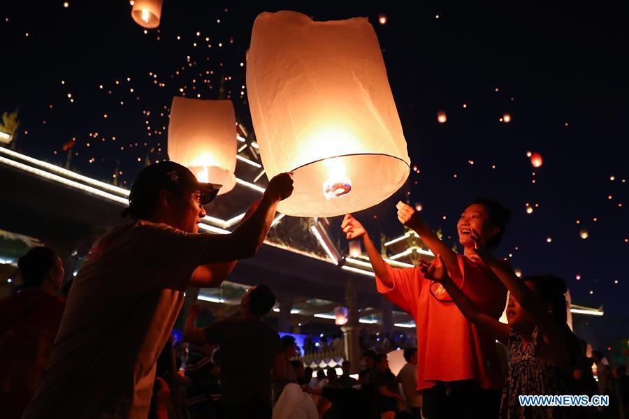 People fly Kongming lanterns by Lancang River in Yunnan