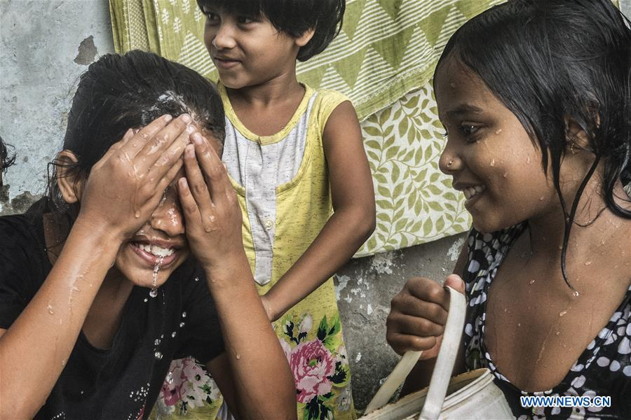 Indian children cool themselves in hot summer afternoon