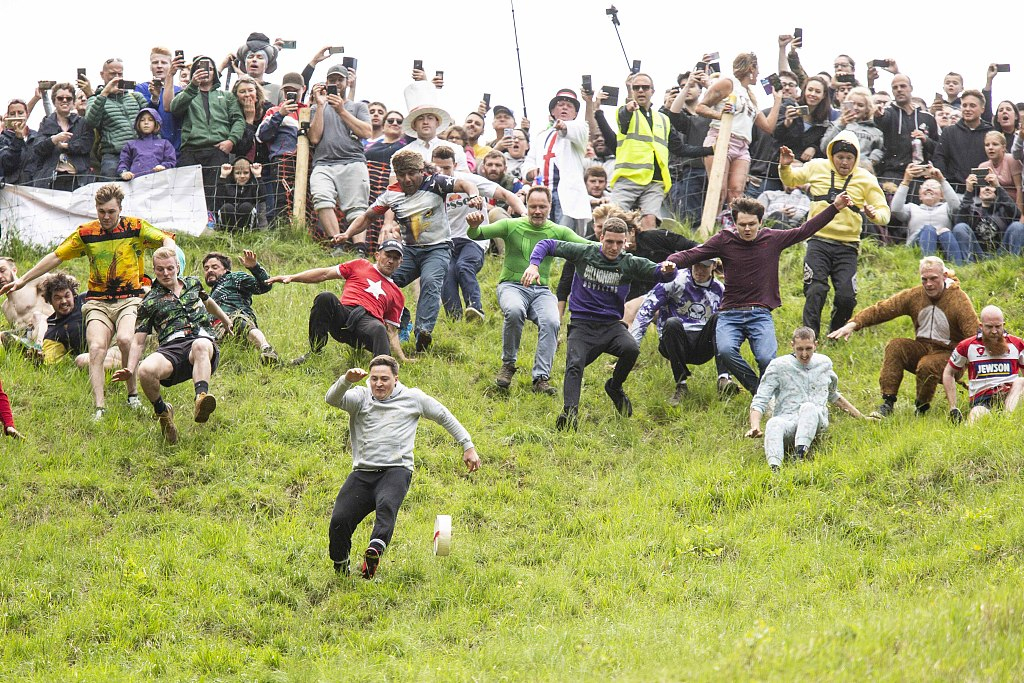 'Throw yourself off the top': daredevils enter cheese-rolling race