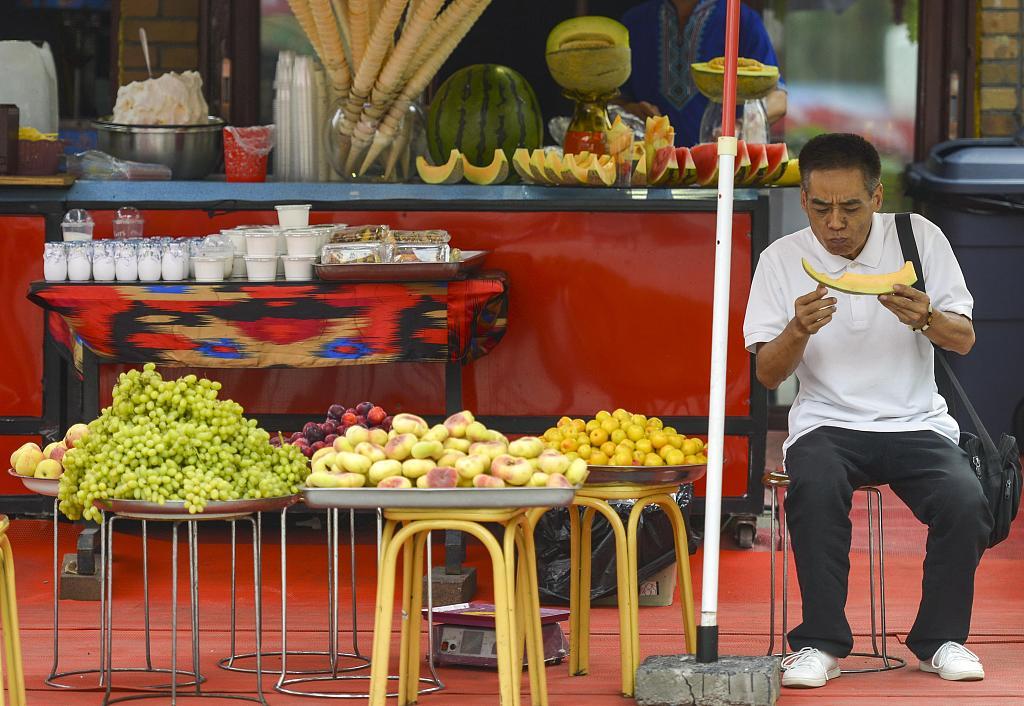 2019年7月8日,位于新疆乌鲁木齐市二道桥的国际大巴扎,一水果摊位前,游客正在品尝哈密瓜。 刘新(新疆分社)_中新社_视觉中国.jpg