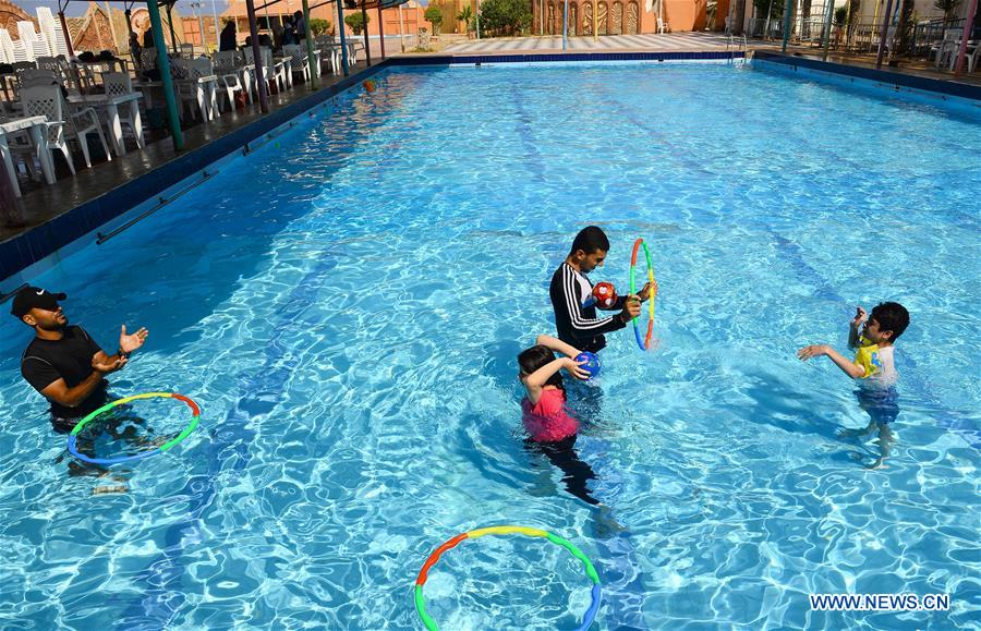 Palestinian swimming instructors teach children with autism in pool in Gaza Strip city