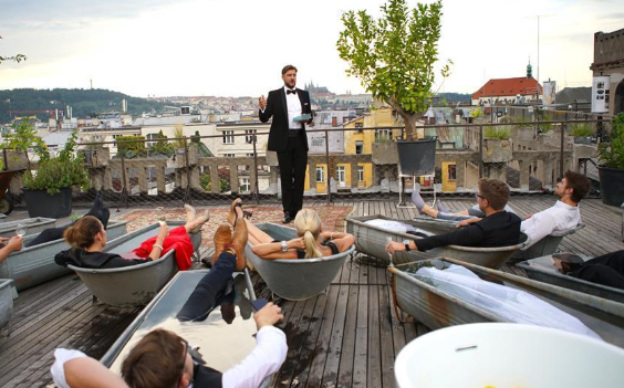 Audience watch performance in hot tubs on roof of building in Prague