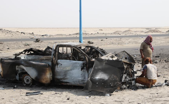Local people check cars destroyed during airstrikes on outskirts of Aden, Yemen