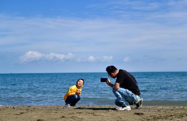 Tourists enjoy scenery along Qinghai Lake during Mid-Autumn Festival holiday