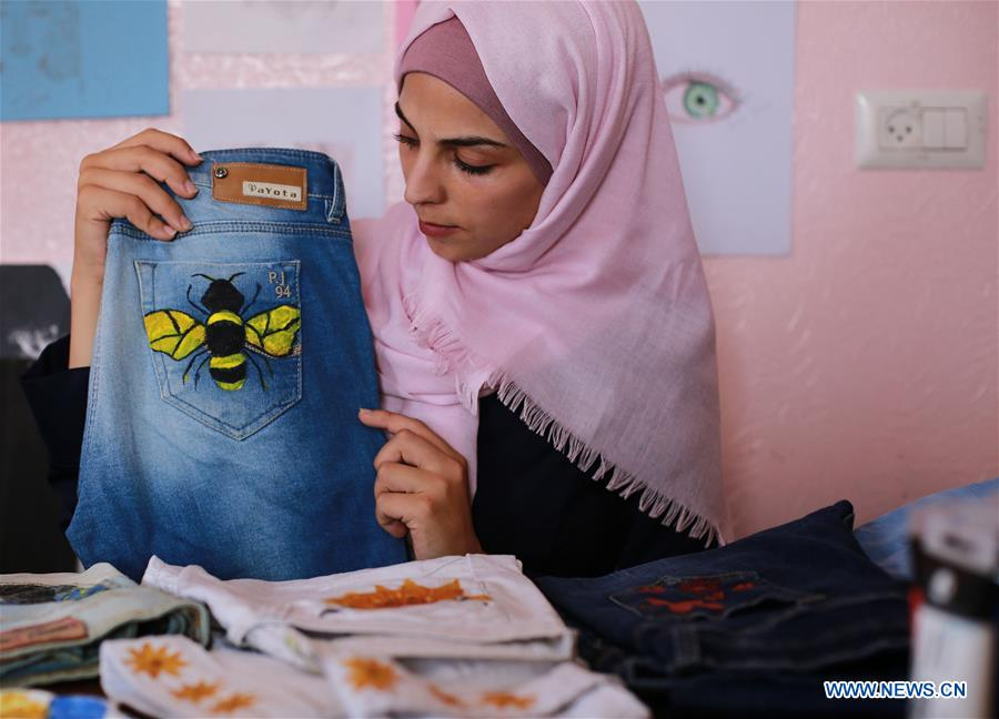 Palestinian artist paints on jeans in Gaza Strip city of Khan Younis
