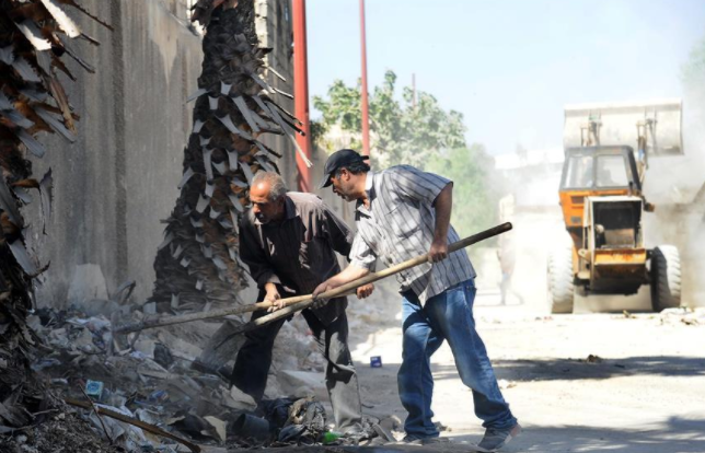 Syrian workers remove rubble from neighborhood of al-Qadam in Damascus