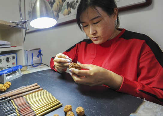 Craftswoman dedicated to fruit pit carving for over 2 decades