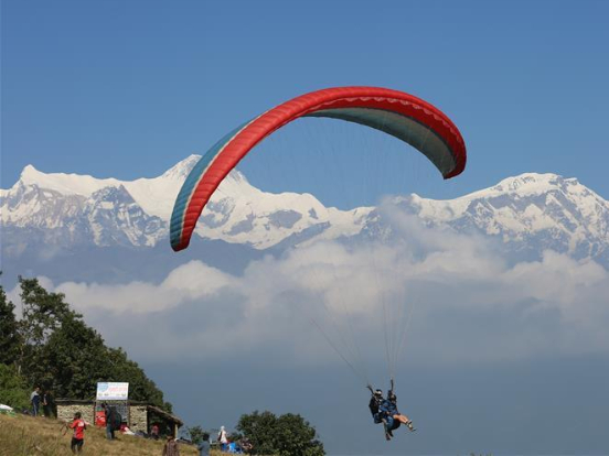 Tourists experience paragliding in Pokhara, Nepal