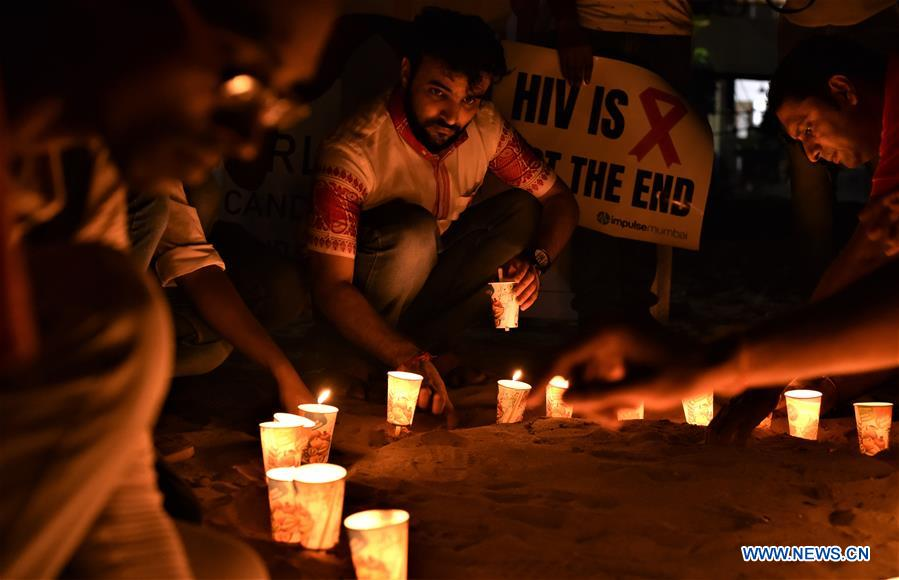 Volunteers light candles on World AIDS Day in Mumbai, India