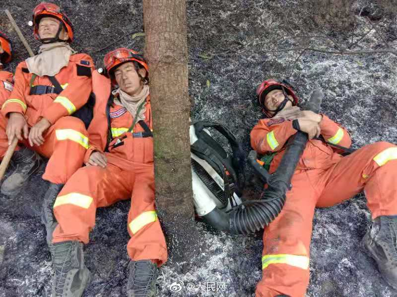 Firefighters exhausted after putting out a mountain fire in South China