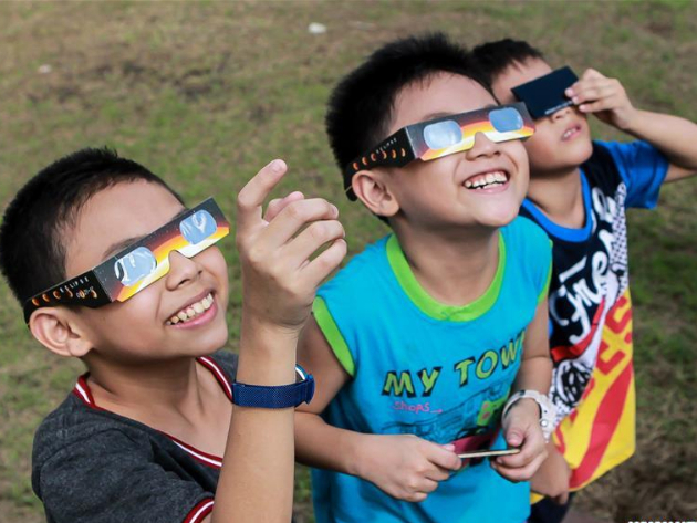 People watch partial solar eclipse in the Philippines