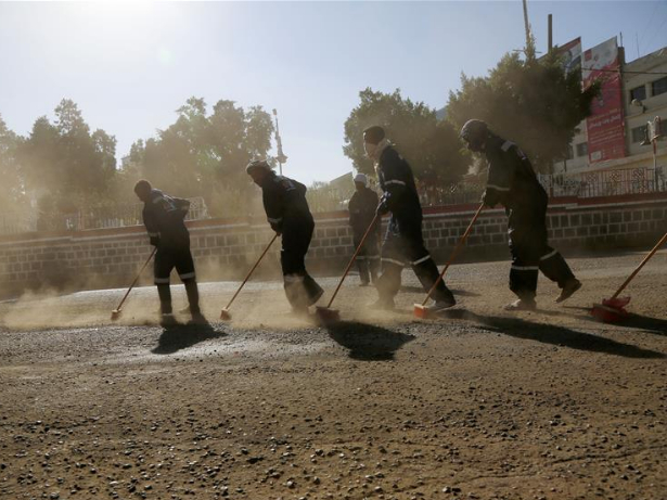People clean street during cleaning campaign in Sanaa, Yemen