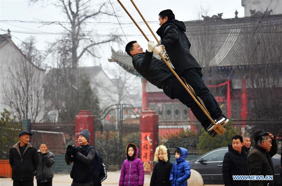 Villagers play on swing as tradition to greet upcoming Spring Festival in NW China