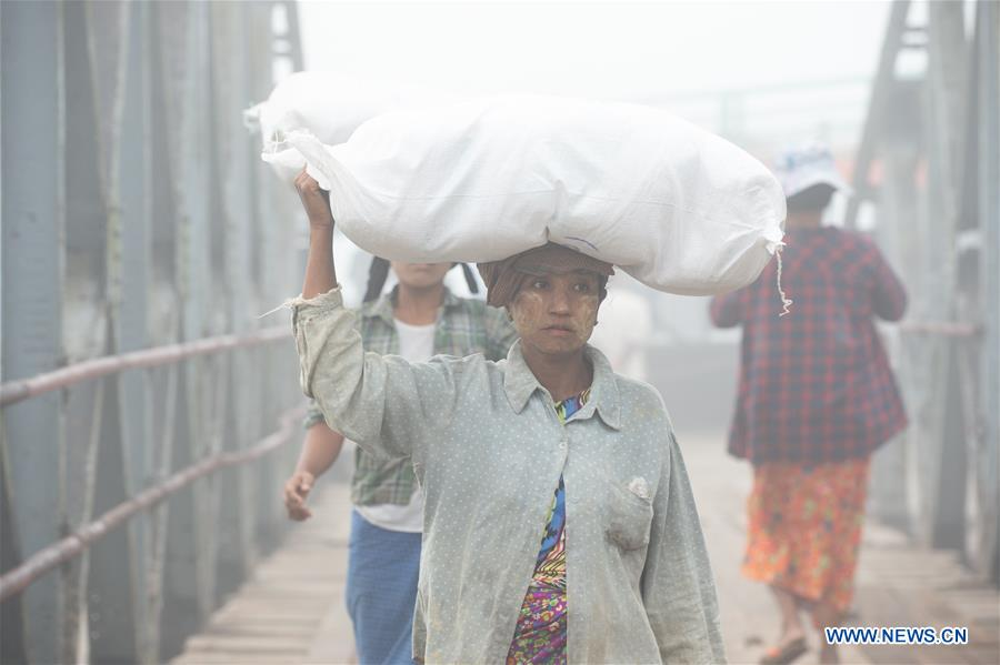 Female laborers unload goods from cargo ship at pier in Kyaukpyu, Myanmar