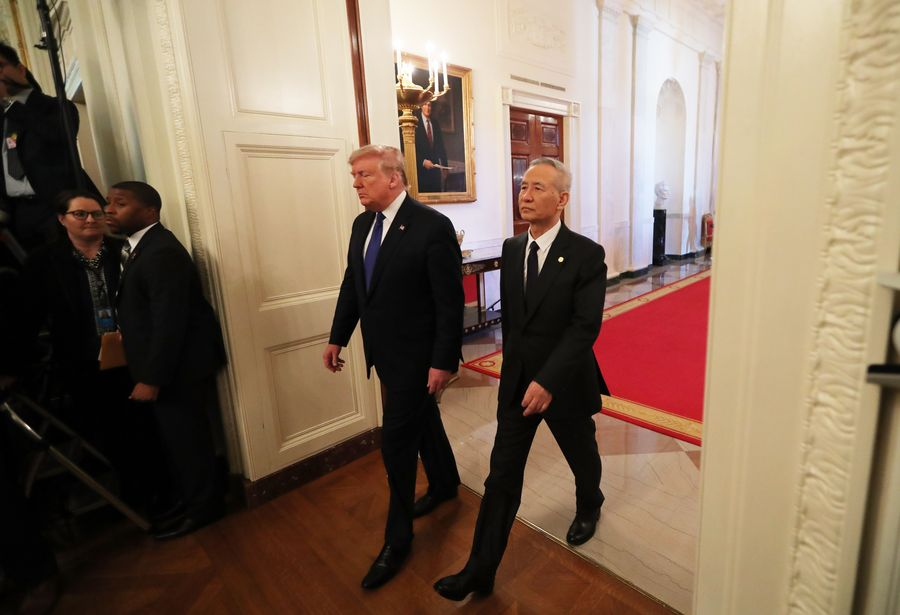 Chinese Vice Premier Liu He, US President Donald Trump walk into White House East Room for trade deal signing