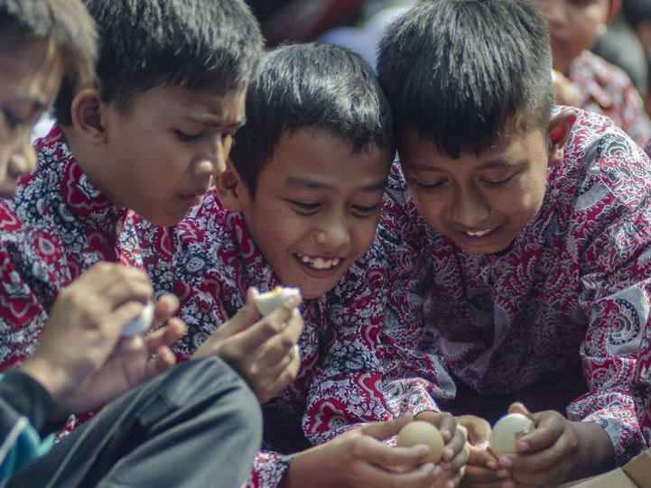 Indonesian students eat steamed eggs for extra nutrition in Bandung