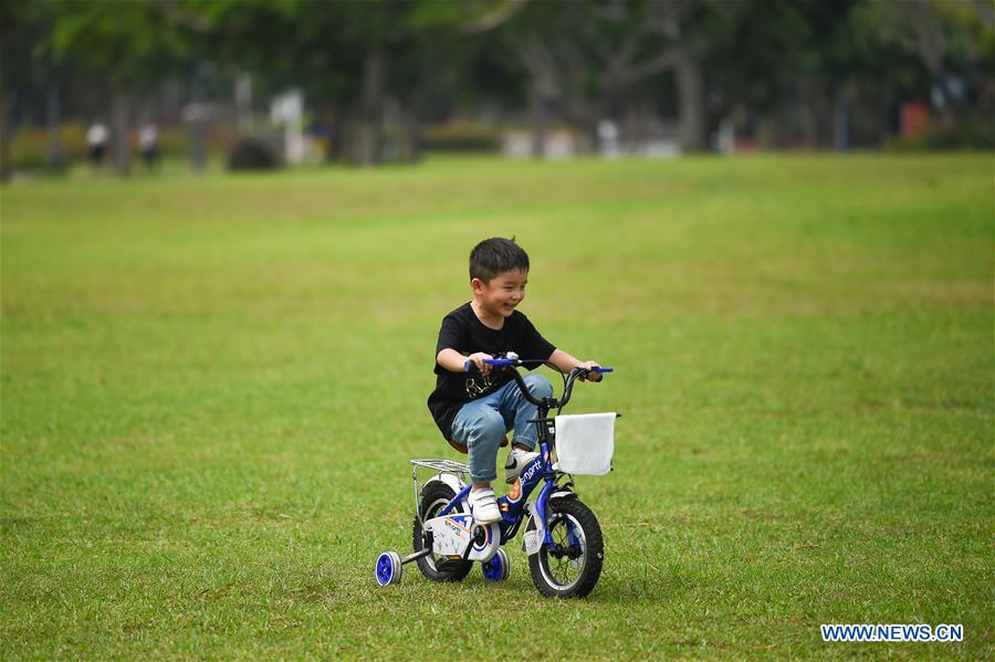 People enjoy leisure time at Evergreen Park in Haikou