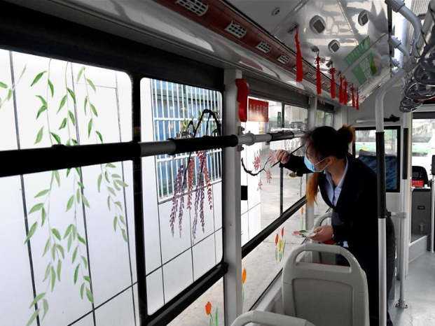 Bus conductor in Zhengzhou paints flowers on bus window as spring comes