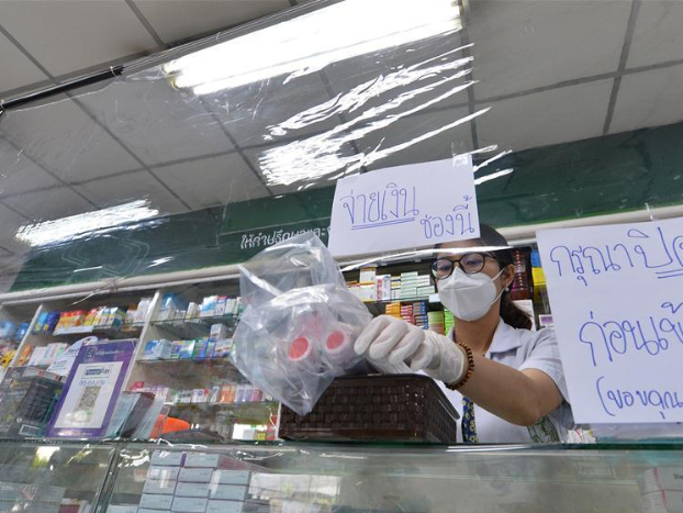 Clerk uses plastic sheets to serve customer in Bangkok, Thailand