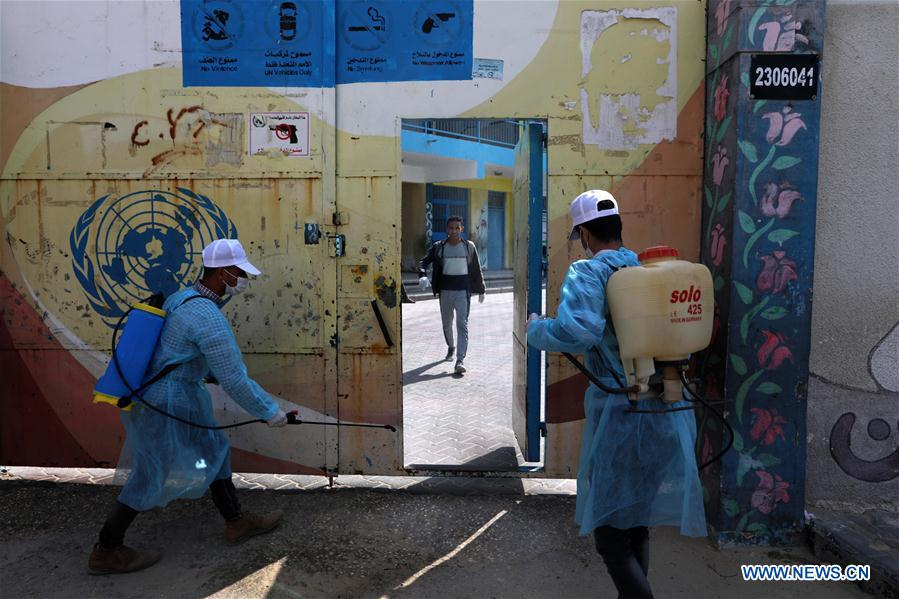 Palestinian volunteers disinfect entrance of school amid spread of COVID-19