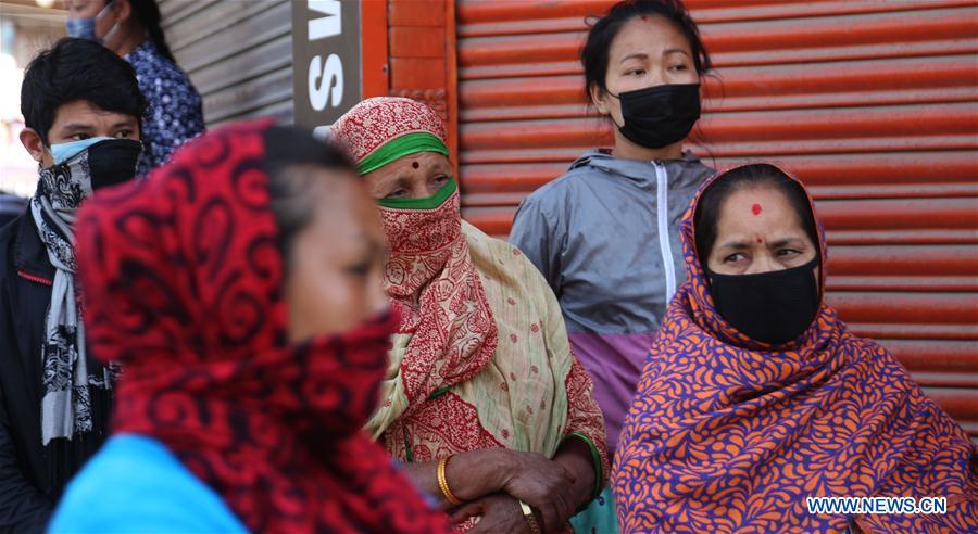 People wait to receive food in Kathmandu, Nepal