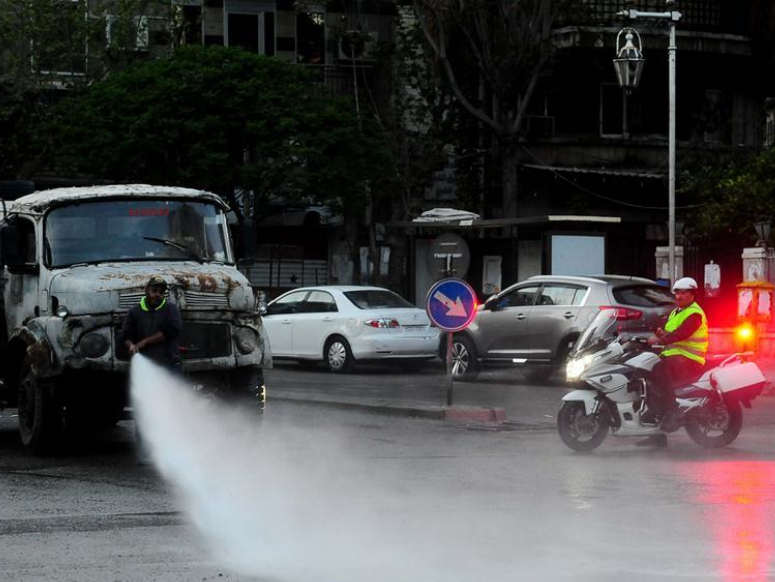 Workers sanitize street with water to prevent spread of COVID-19 in Damascus