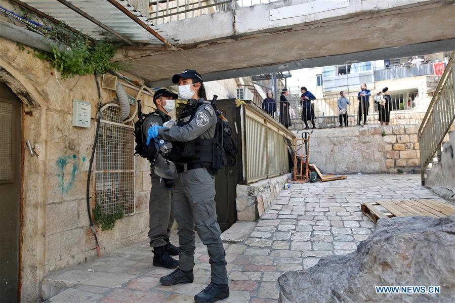 Israeli police officers patrol on street in Mea Shearim neighborhood in Jerusalem