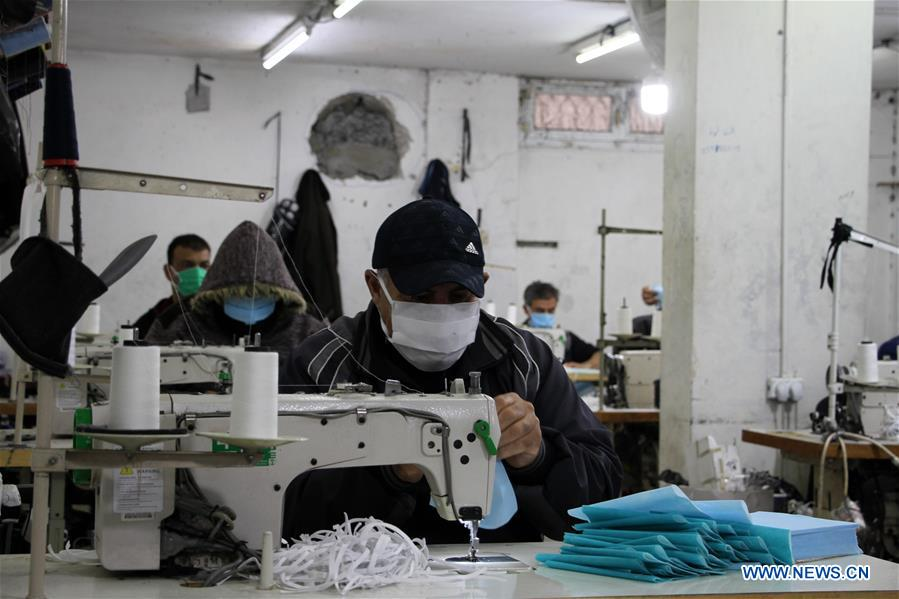 Palestinian workers make face masks at factory in Gaza City