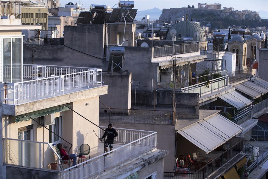 Greeks enjoy sunshine at balconies amid COVID-19 epidemic