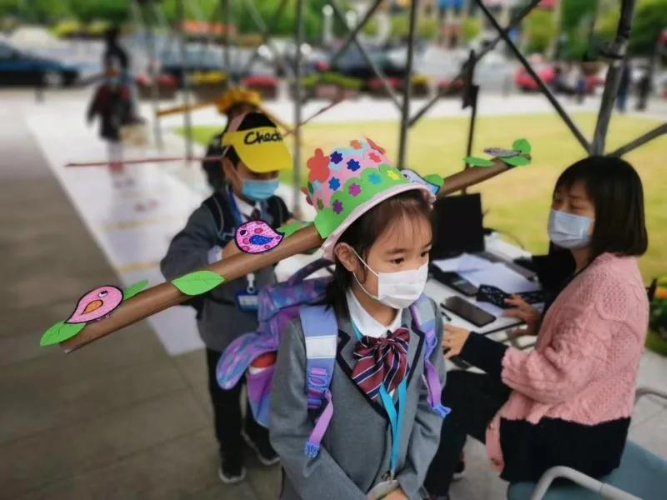 Students in Hangzhou wear special hats to maintain social distancing as school resumes
