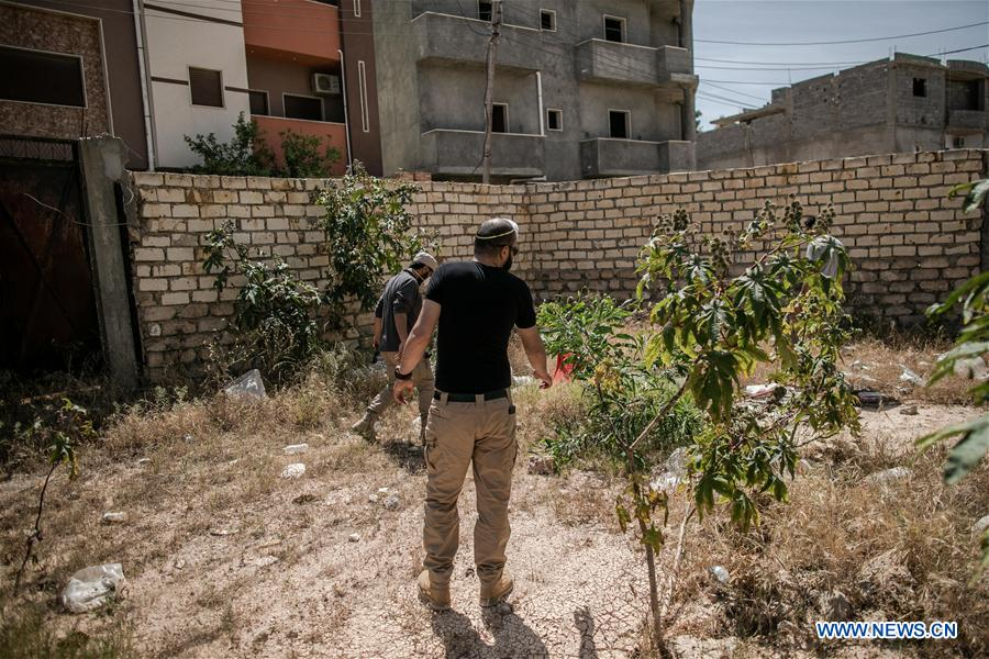 Explosives experts seen during search for unexploded shells in Tripoli, Libya