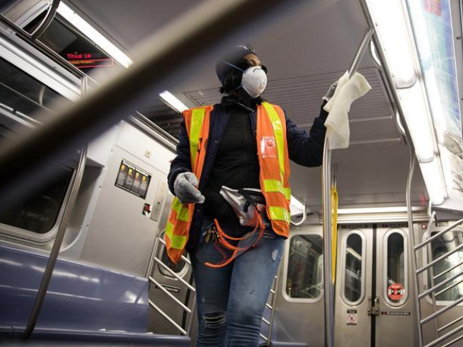 Workers disinfect train at subway station in New York City