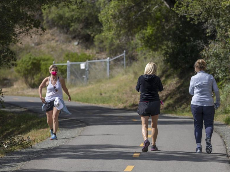 People walk along trail at park in San Mateo County, US