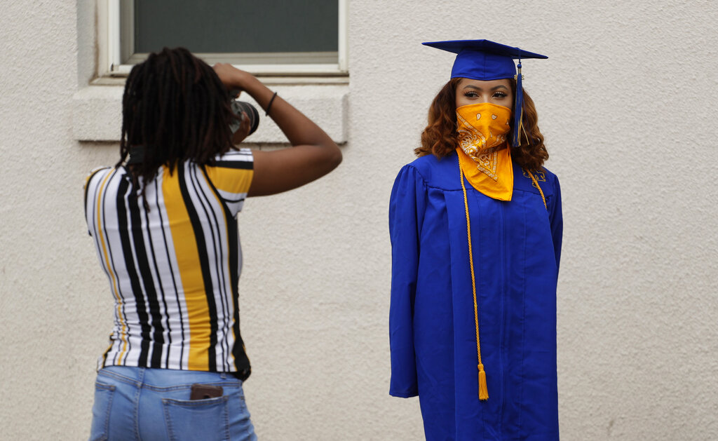 Anderson High School senior Teyaja Jones, right, poses in her cap and gown and a bandana face cover, Tuesday, May 5, 2020, in Austin, Texas. Texas' stay-at-home orders due to the COVID-19 pandemic have expired and Texas Gov..jpg