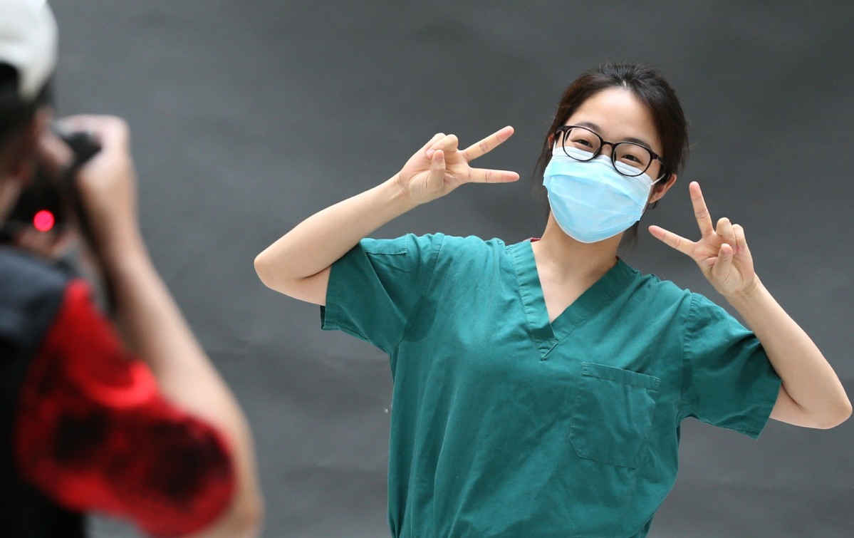Wuhan medical staff shine for the camera on World Smile Day