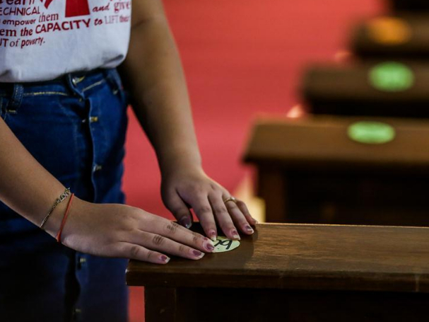 Volunteer puts markers on church pews to ensure social distancing amid COVID-19 pandemic