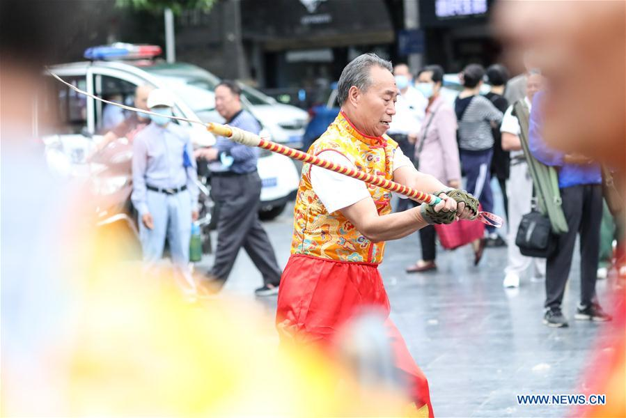 Members of Guiyang Kylin Peg-Top Whipping Club whip a gigantic peg-top