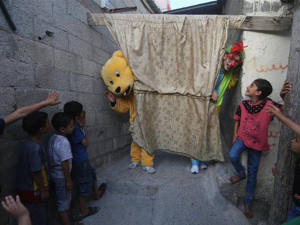 Palestinian volunteers perform for refugee children to lift their spirits in Rafah