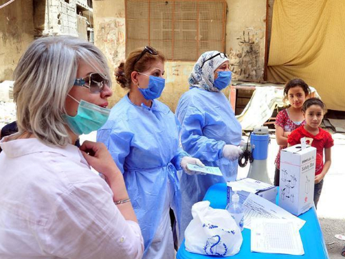 Medical workers give vaccines to children in Damascus