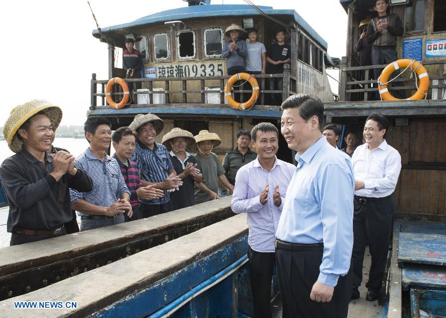 Chinese President Xi Jinping enquires fishermen about their work and life of fishing on a fishing boat at a dock in Tanmen Town of Qionghai City, south China's Hainan Province, April 8, 2013..jpg