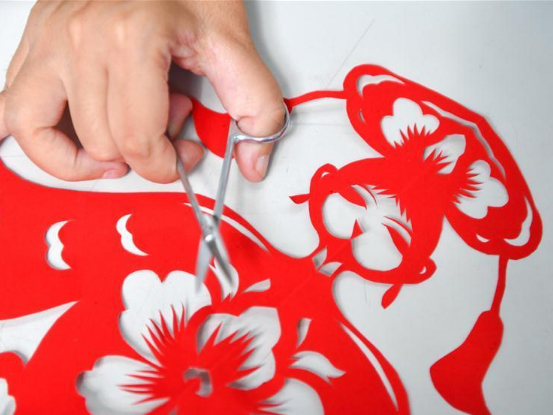 Disabled artist makes papercutting work in Jilin