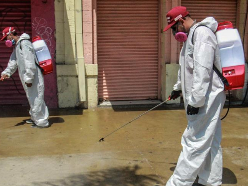 Workers sanitize street in Tijuana, Mexico