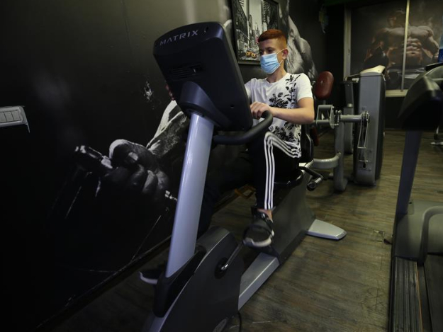 People wearing protective masks exercise in gym in Jerusalem
