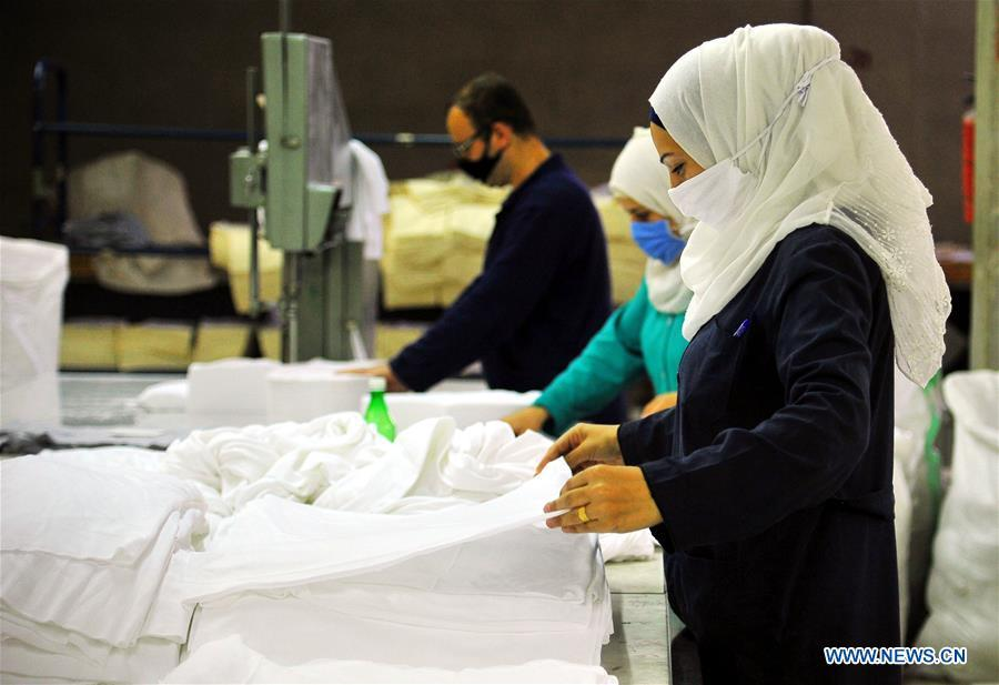 Syrian workers arrange cotton fabric for making masks in Damascus