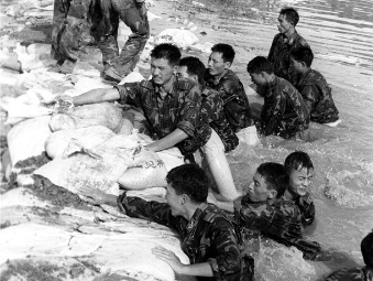 Soldiers fighting floods, then and now