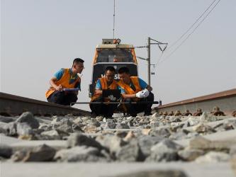 Railway maintenance workers check track on Golmud-Korla railway line in NW China's Xinjiang