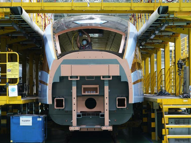 Technicians work on high-speed trains production line in Tangshan, Hebei