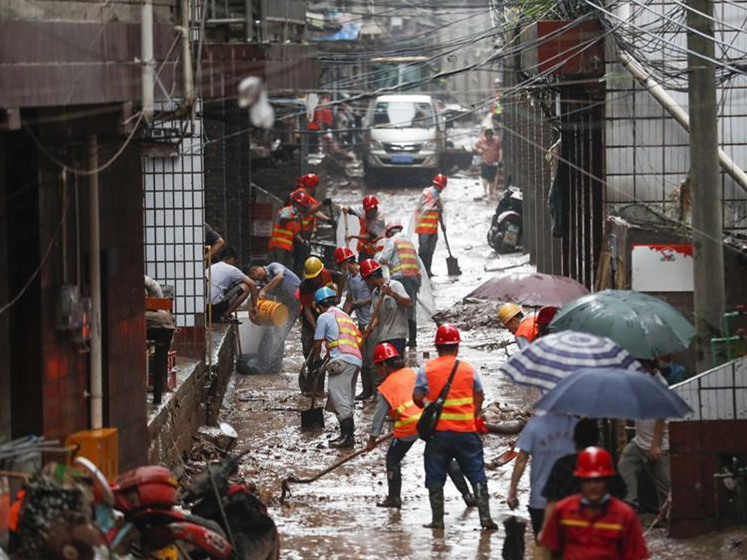 Rescuers help local residents clear debris after flood in Chongqing