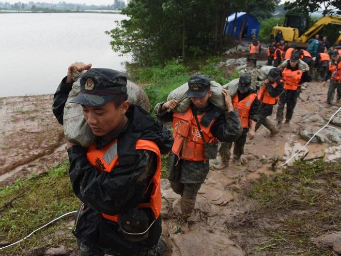 Armed policemen carry sandbags on embankment of Shiba River in Anhui