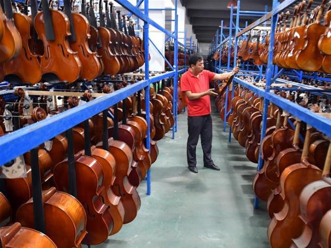 People work at Queshan Violin Industrial Park in Henan